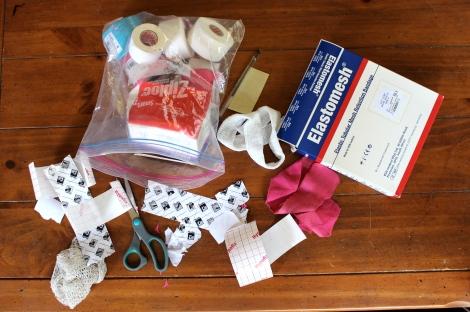 My arsenal: k-tape, hypafix, zinc oxide tape, elastomesh, scissors.